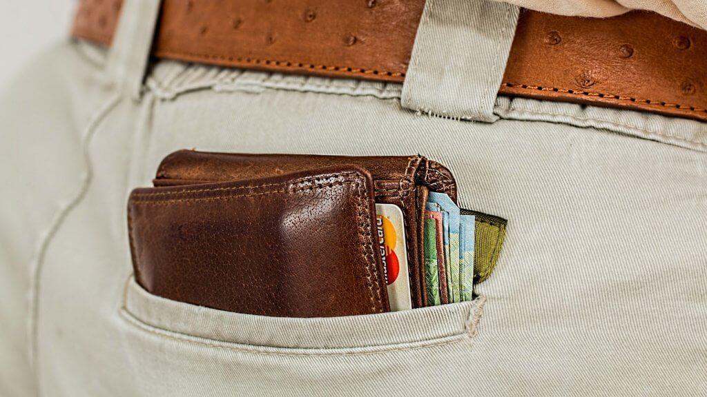Peněženka v kalhotách plná peněz a kreditních karet