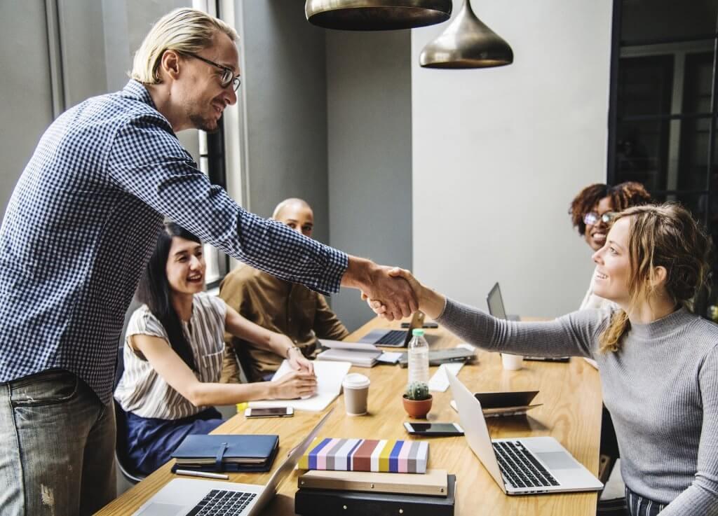 Muž podává ruku ženě na pracovní schůzce